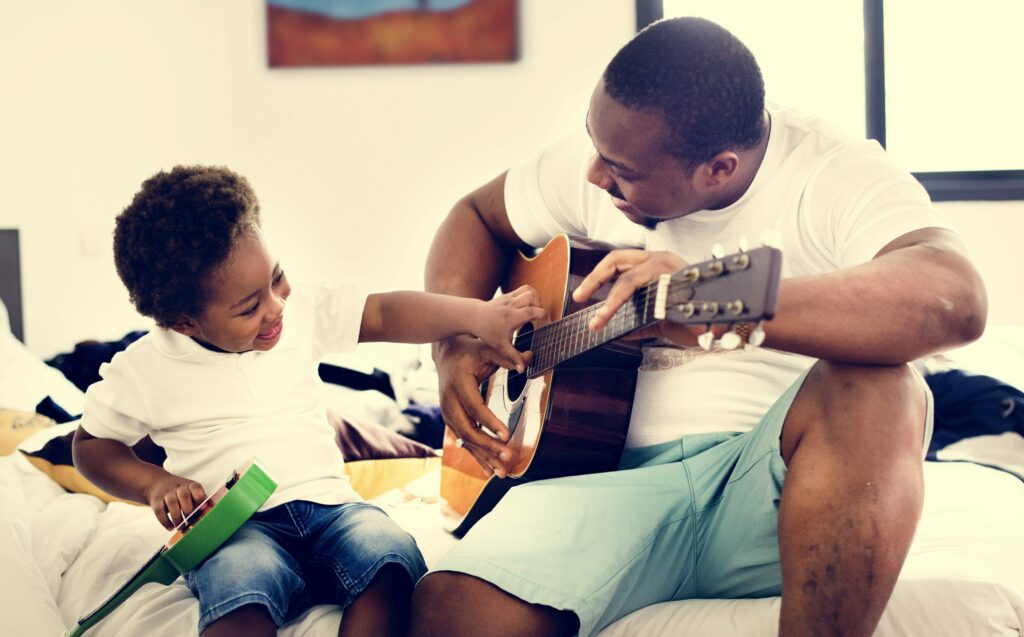 father and son playing guitar showcasing holidays with preschoolers
