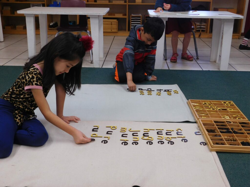 Two kindergarteners working together on third-year lessons at Montessori Center School