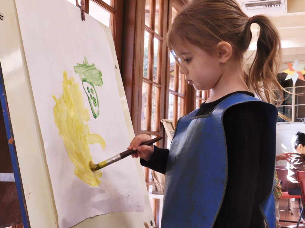 Preschooler painting on an easel during stay-at-home Montessori