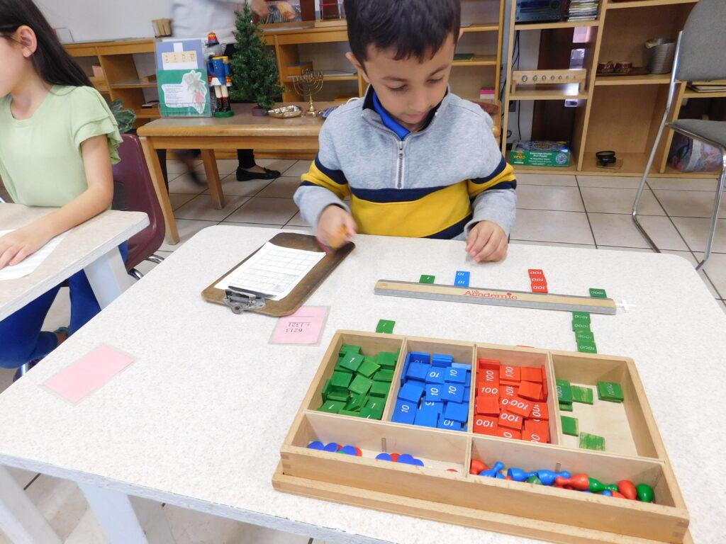 Preschooler practices social distancing while doing Montessori work