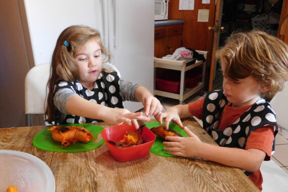 two preschoolers practice chores for children by cutting vegetables