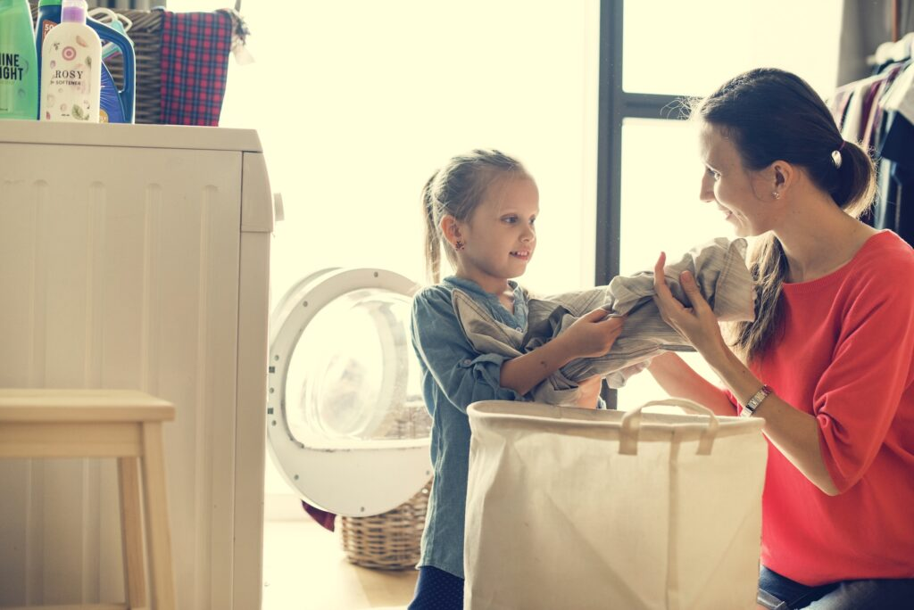 Young girl helps mom with laundry showing chores for children