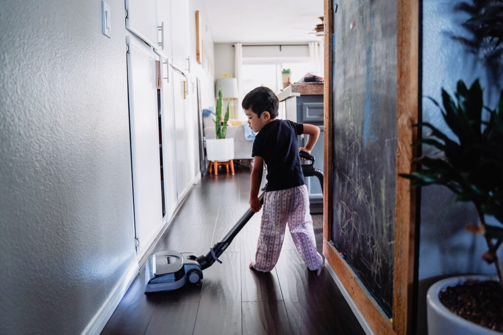 Young boy vacuuming in his house doing chores for children