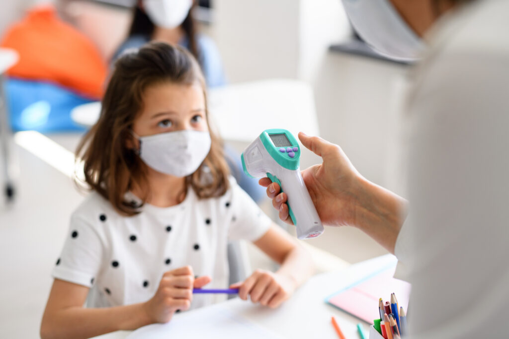 a preschooler wearing a mask and getting her temperature checked showing covid-19 procedures for preschool