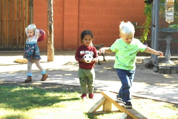 Three toddlers playing outside at a Montessori toddler program in Phoenix