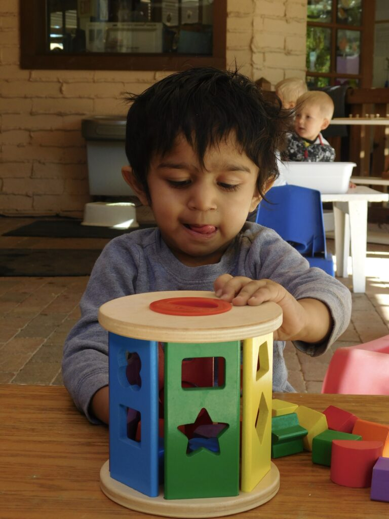 Toddler sorting shapes at a Montessori toddler program in Phoenix