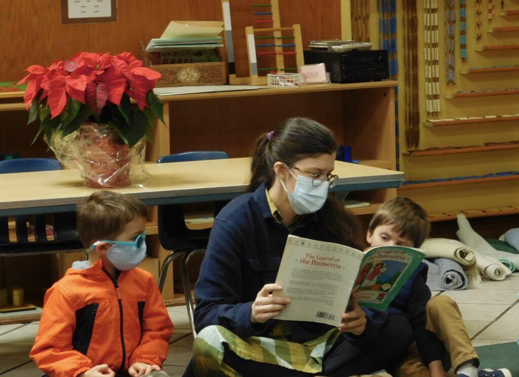 Montessori teacher sits reading books with two Montessori preschoolers