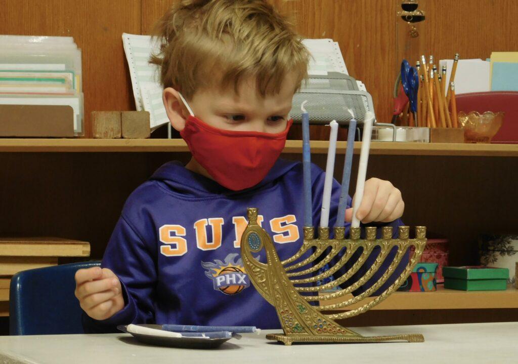 A Montessori preschooler places candles in a menorah in celebration of Hanukkah