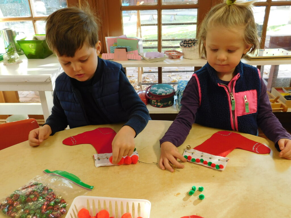 Two Montessori preschoolers decorate stockings during the holiday season at Montessori Center School