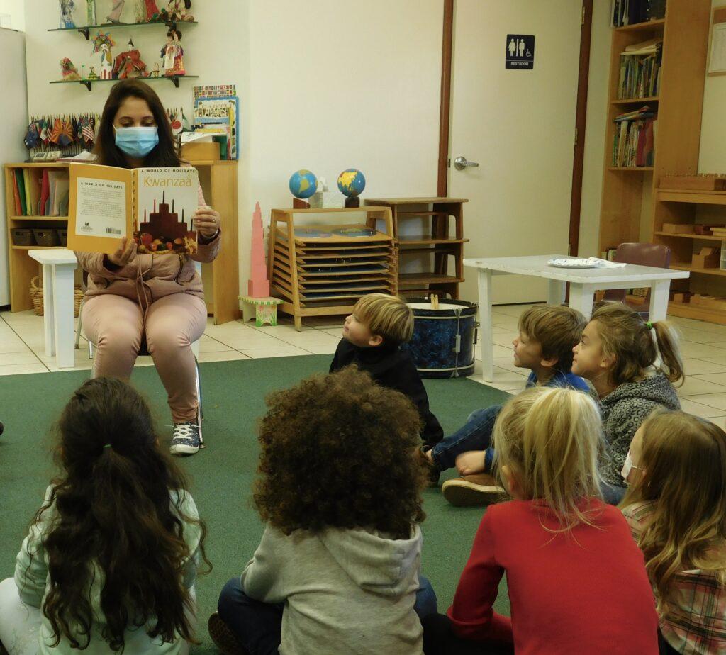 A group of Montessori preschoolers listen as their teacher reads them a story