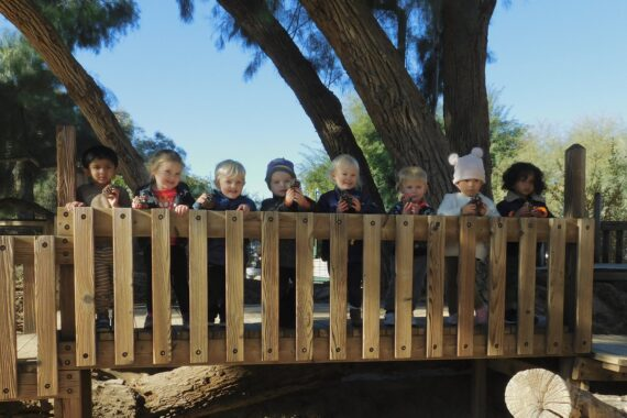 Montessori toddlers gather together on an outdoor deck holding their pinecone decorations