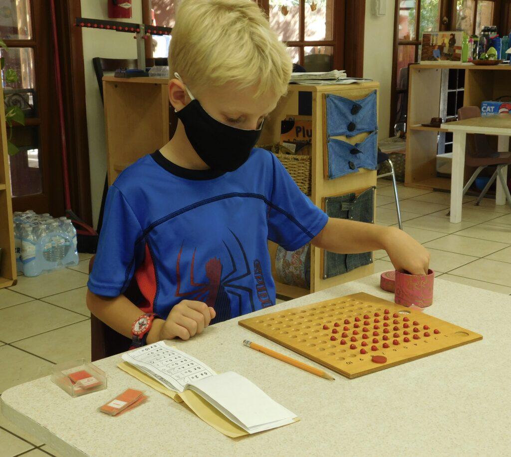 Student at a Montessori kindergarten doing decimal counting work