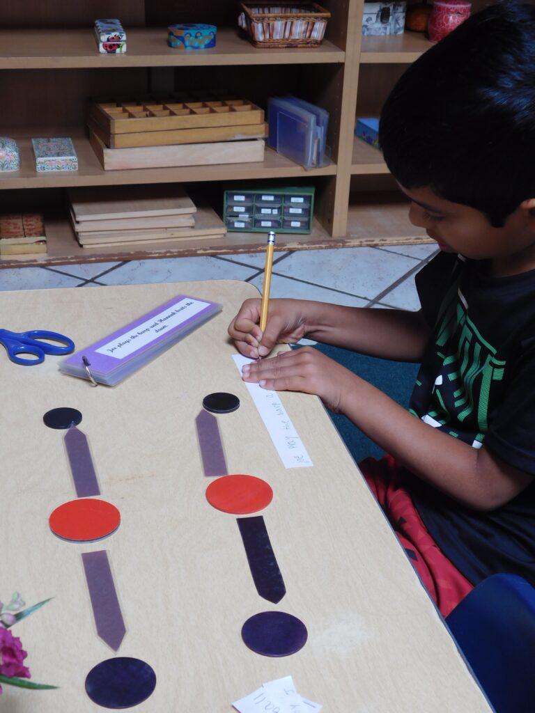 Montessori kindergartener at Montessori Ceenter School doing sentence construction