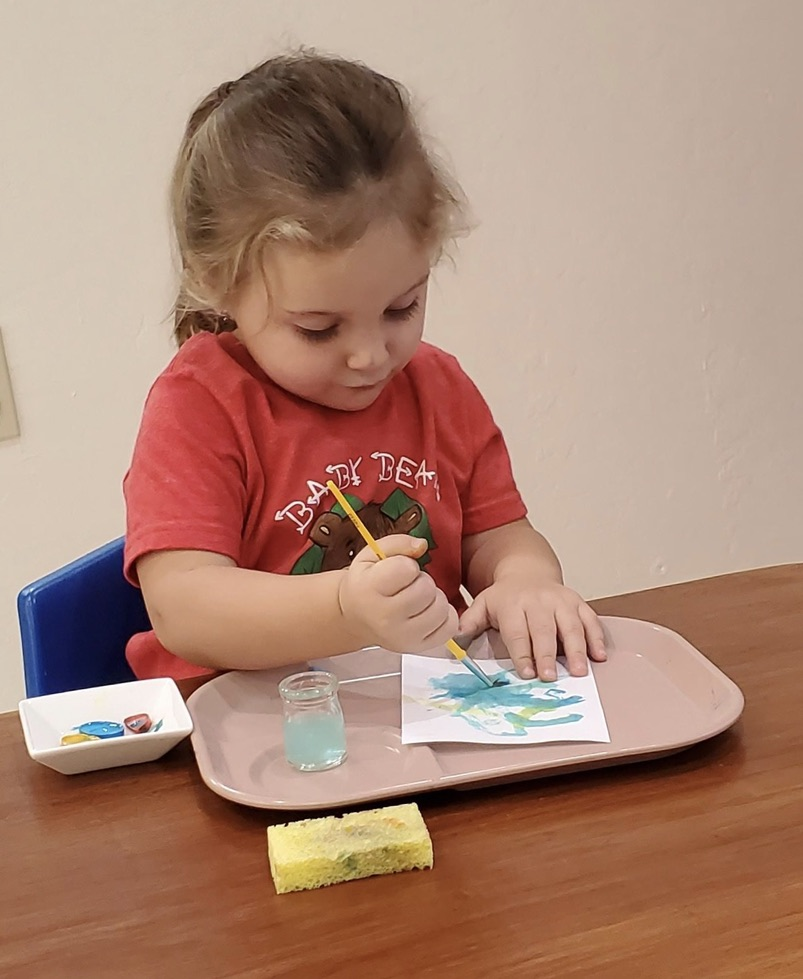 toddler painting independently showing one of the benefits of Montessori for toddlers